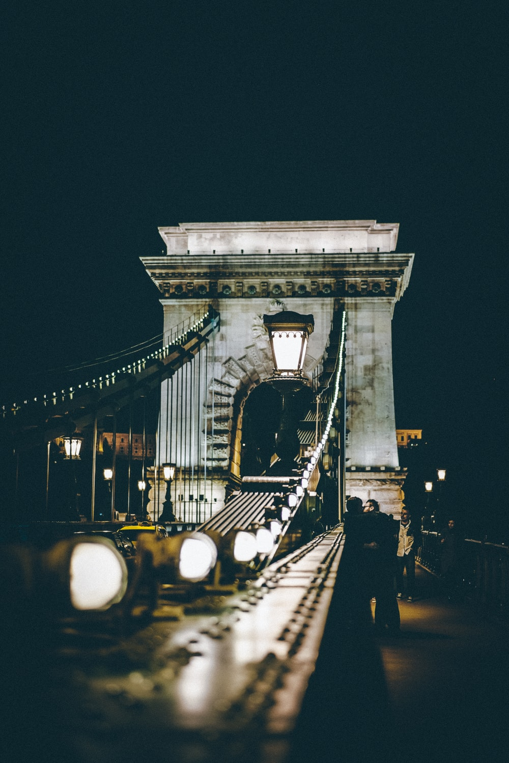 selective photography of bridge at night time