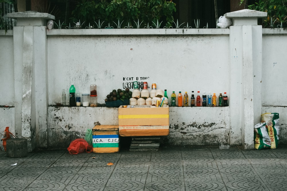 assorted-labeled bottle display on white concrete wall near gray pavement at daytime