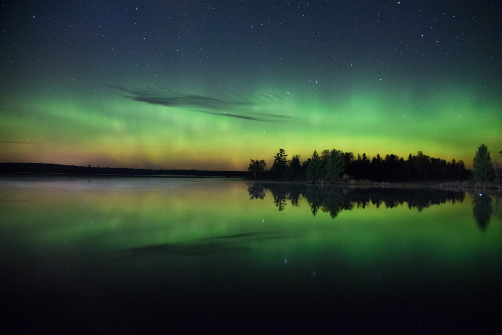 green and yellow aurora borealis reflected on water