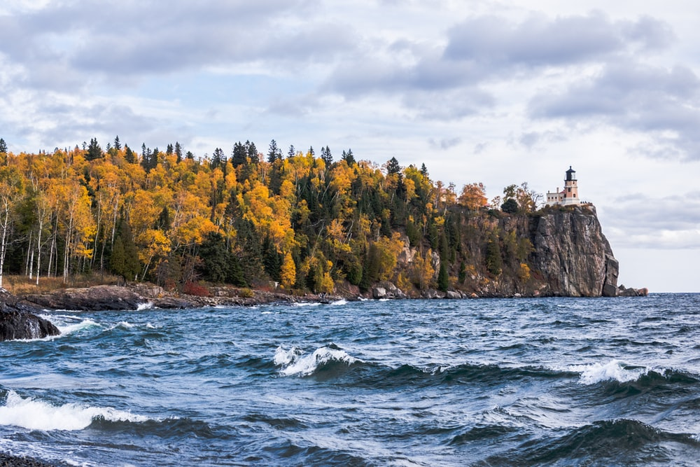 body of water near island with trees and lighthouse