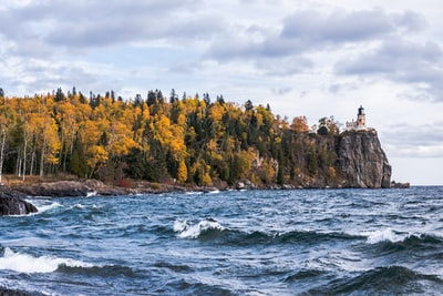 body of water near island with trees and lighthouse minnesota zoom background