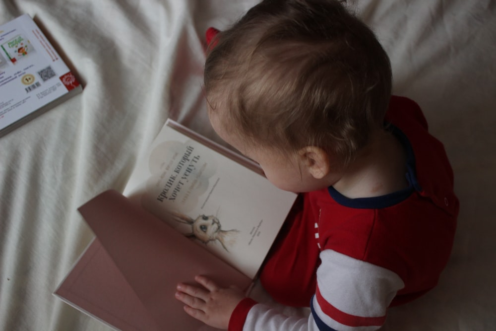 baby sitting on bed while reading on book