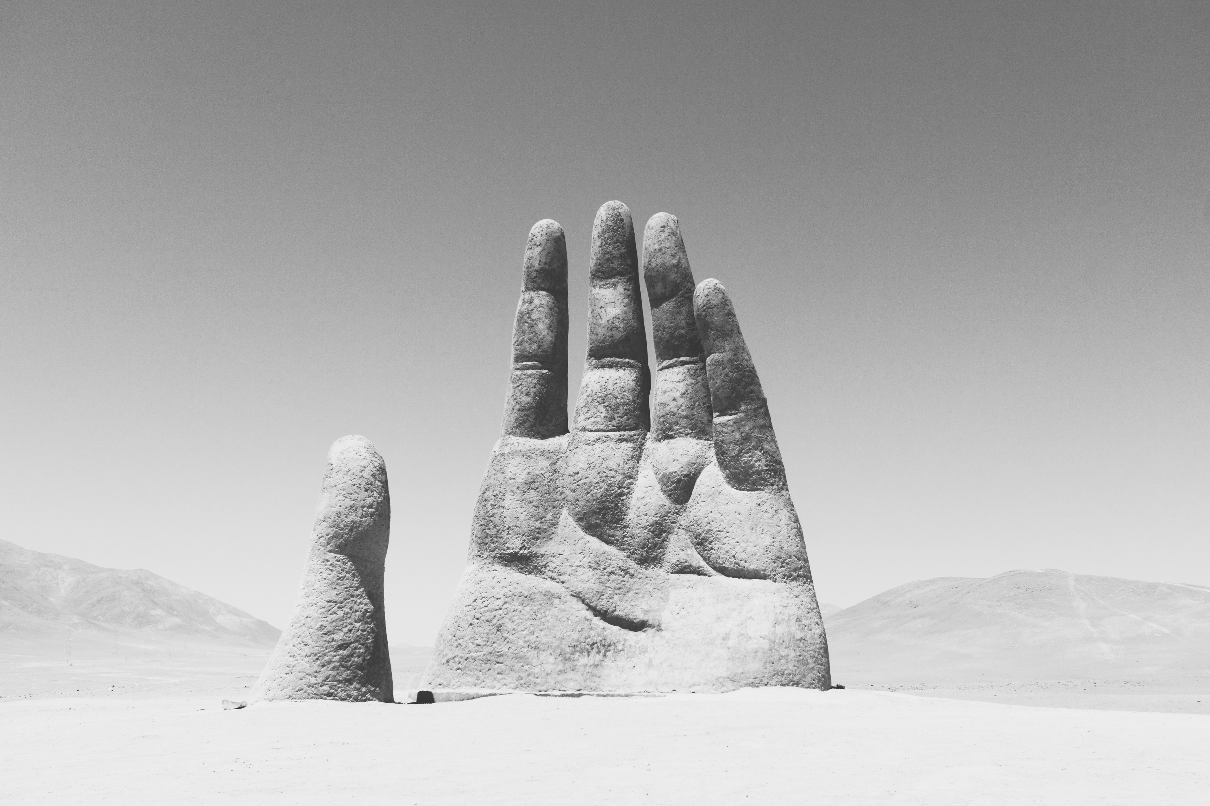 grayscale photography of hand sculpture on sad