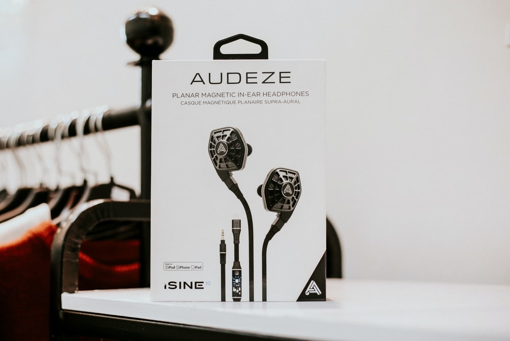 black Audeze earphones box on white wooden surface