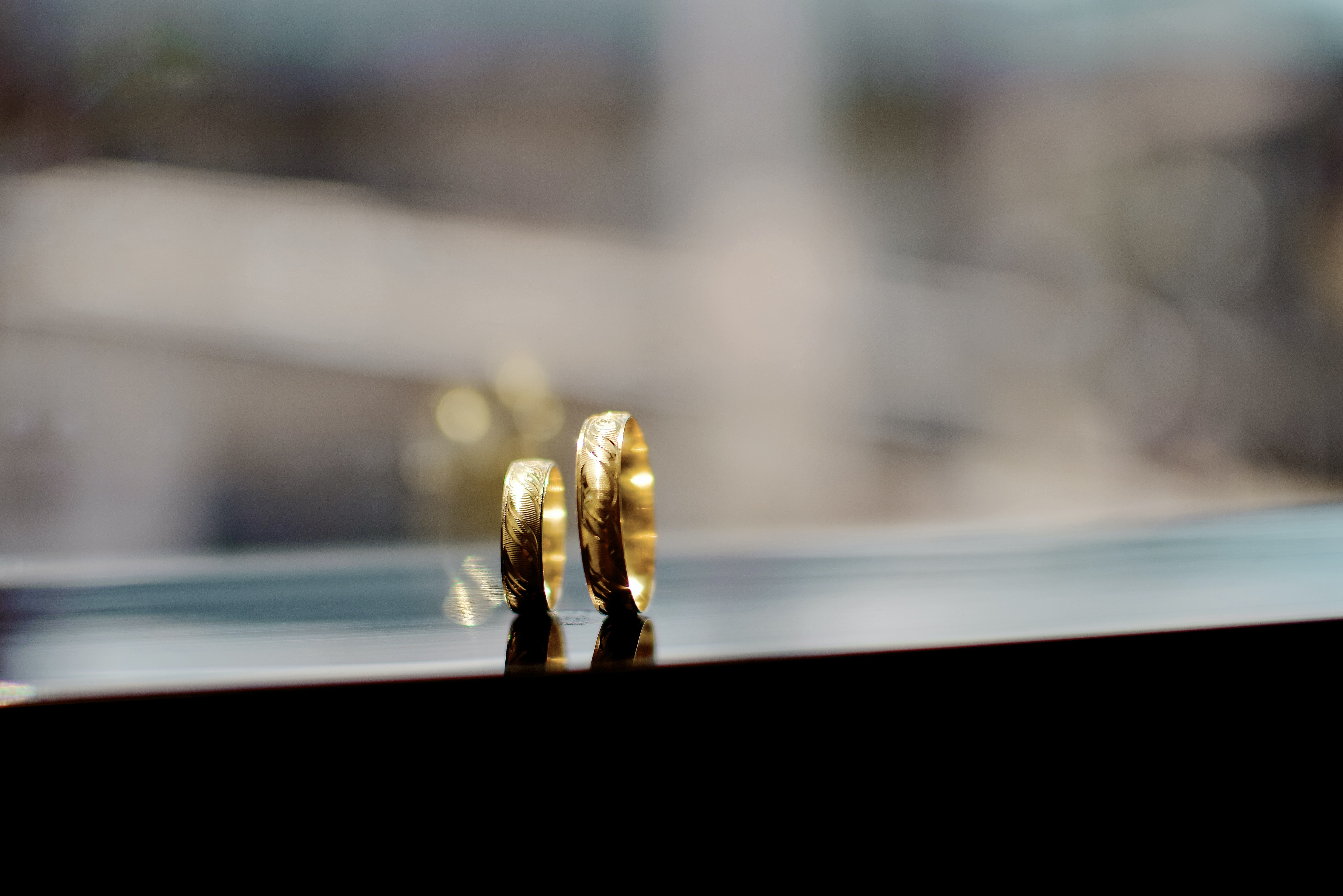 shallow focus photography of gold-colored couple rings