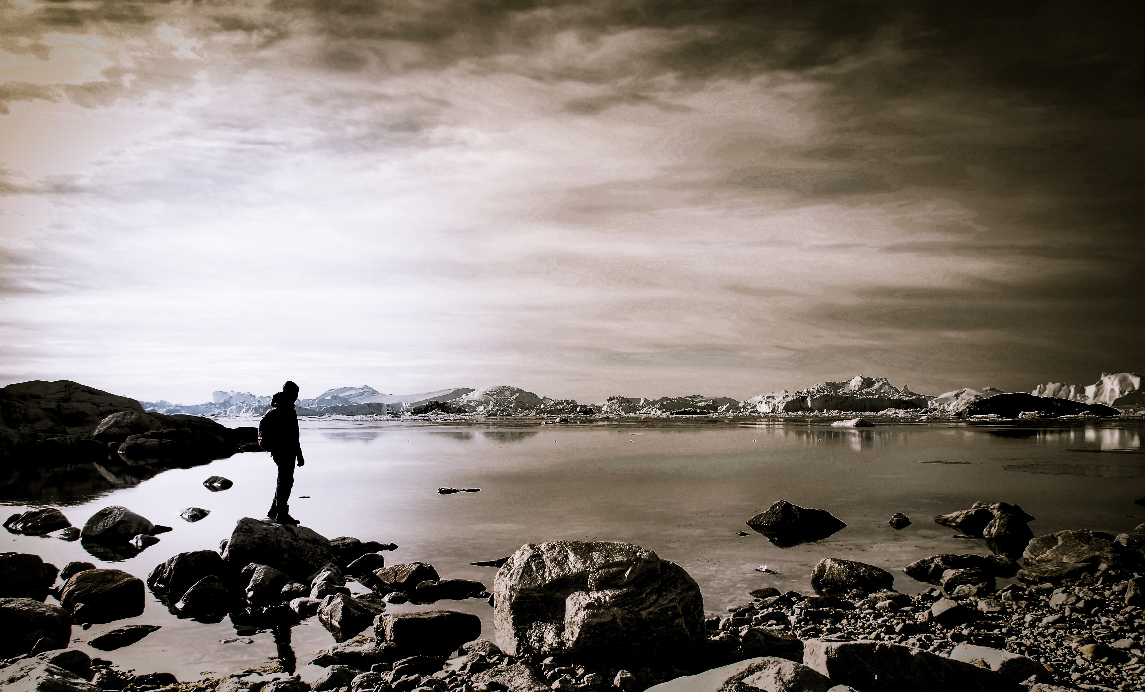 person standing on rock near body of water