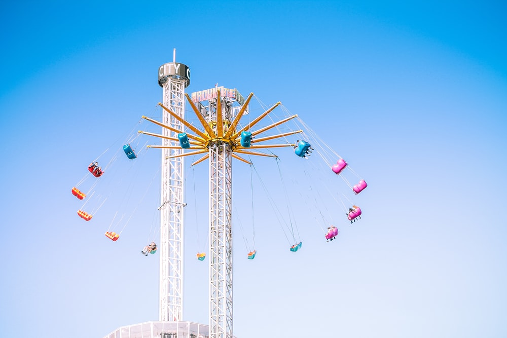 people riding swing amusement ride low-angle photography