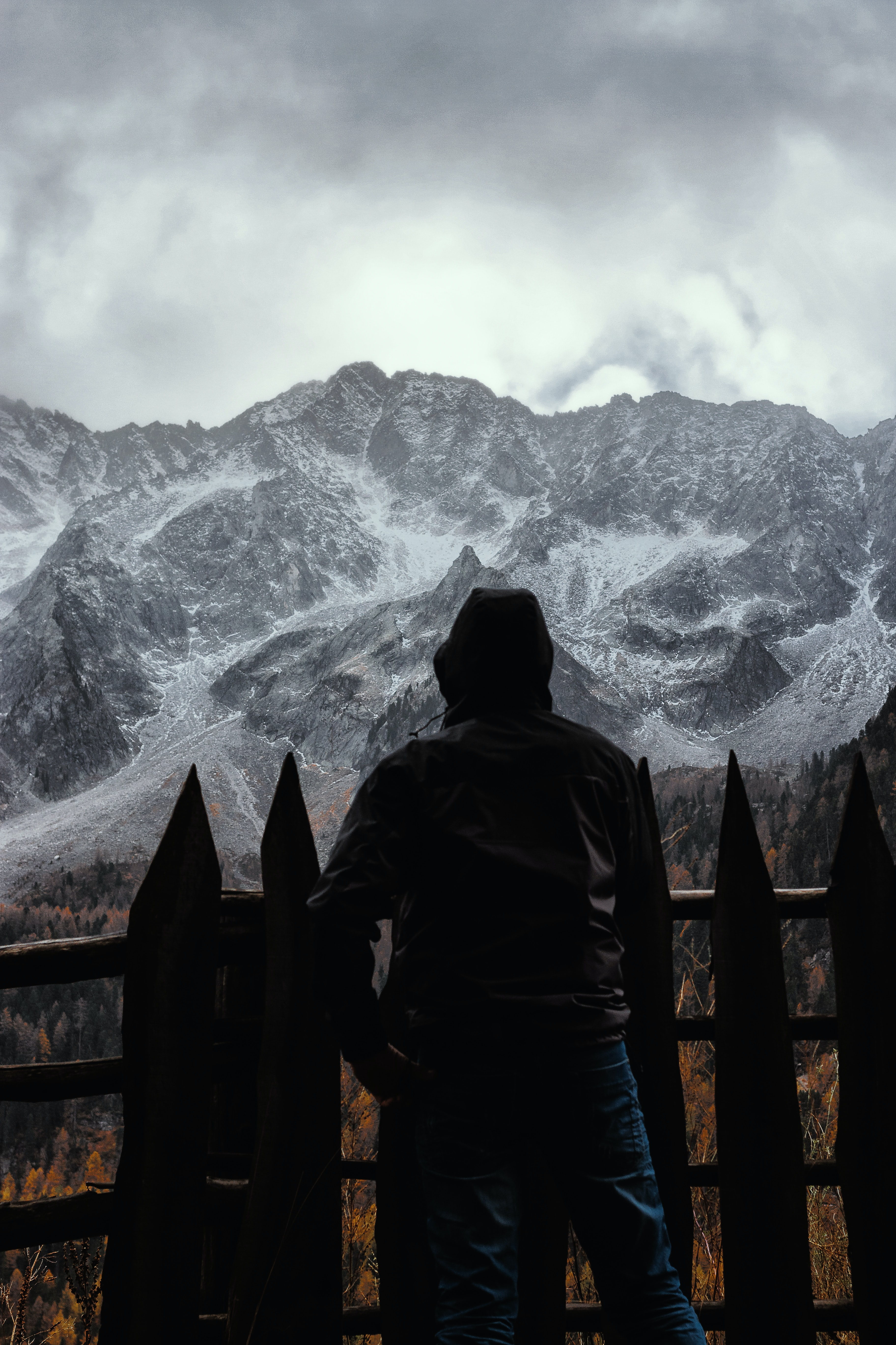 silhouette of person standing in front fence with a scene of mountains
