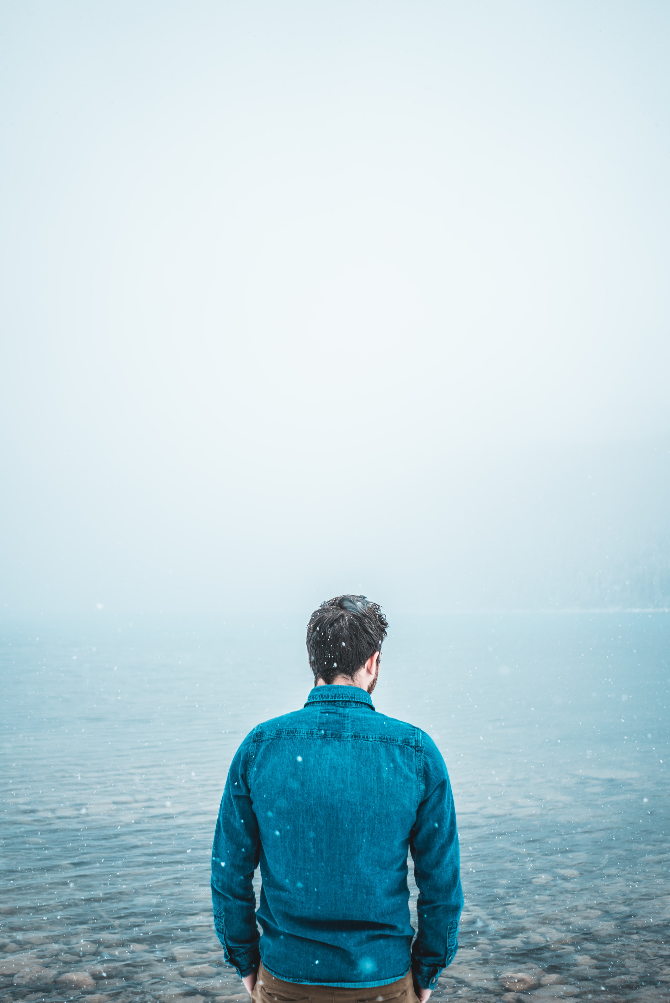 man standing in front of body of waterf