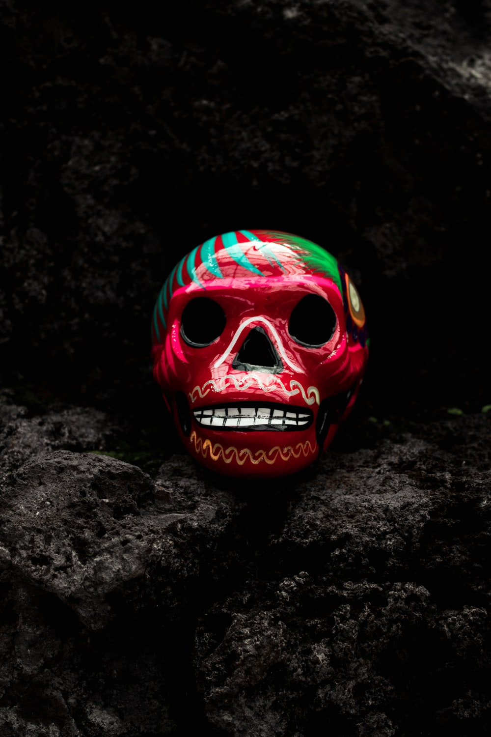 red and green ceramic skull ornament on black rock