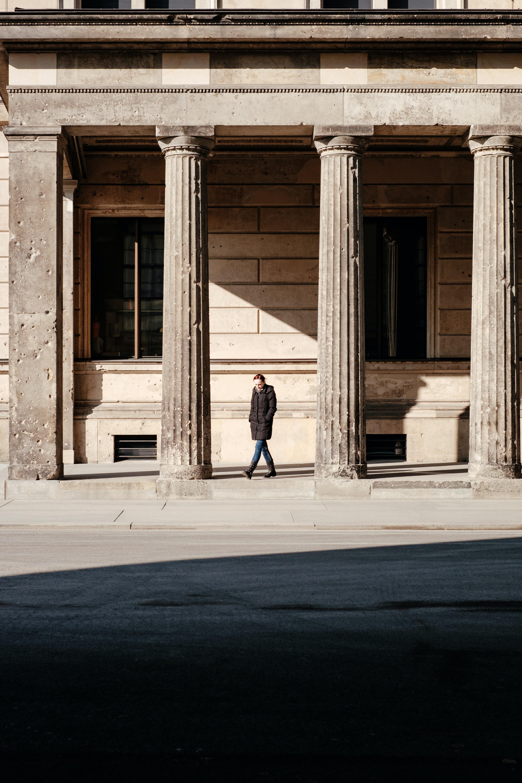 man in black jacket walks on building posts