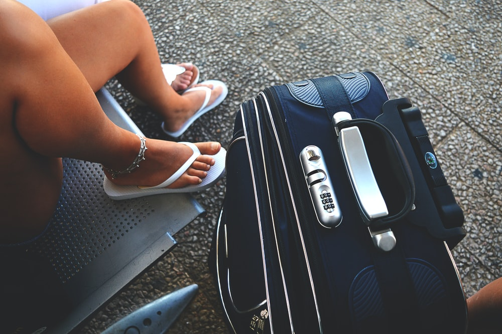 woman sitting on chair beside luggage bag