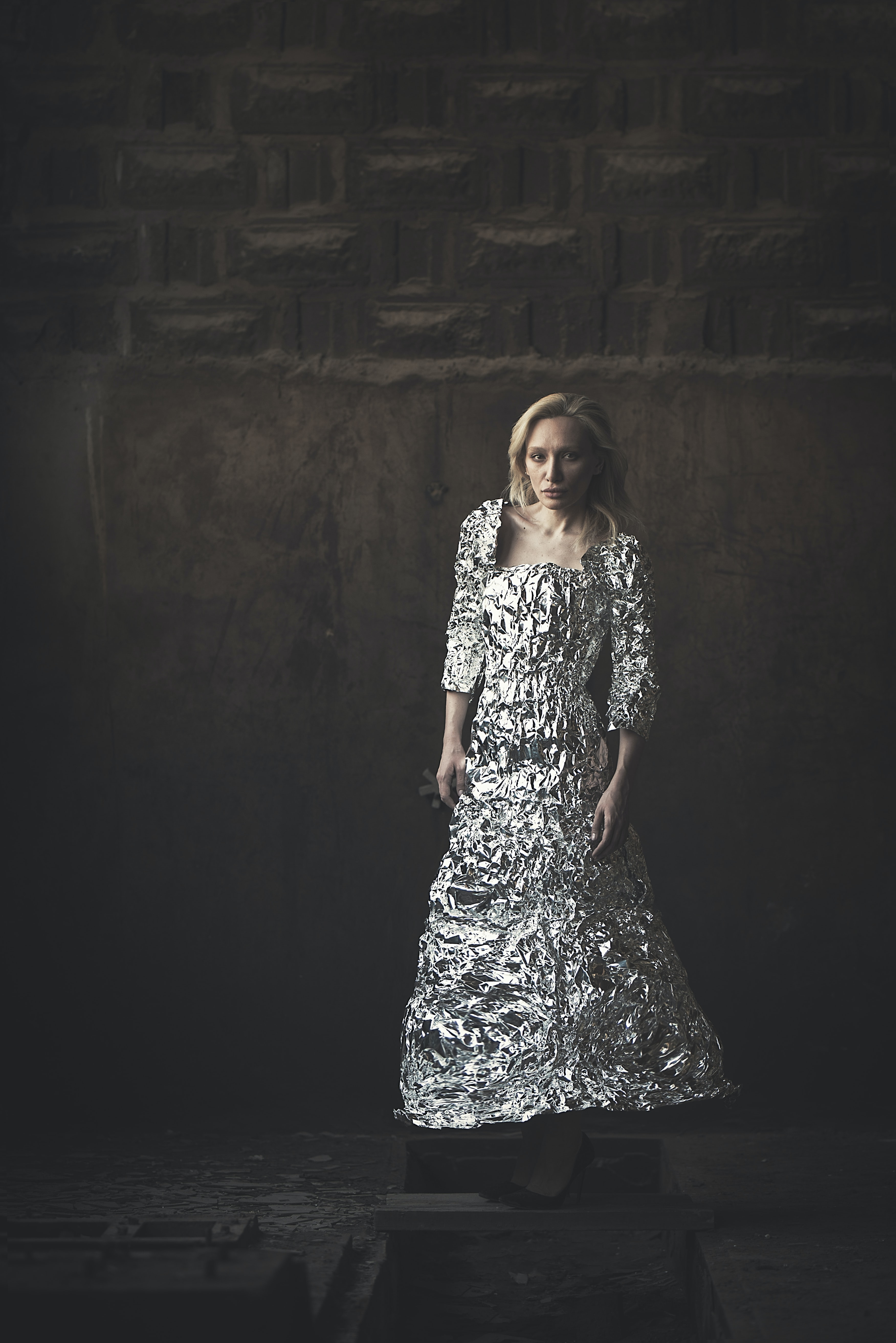 woman with silver quarter-sleeved dress beside wall