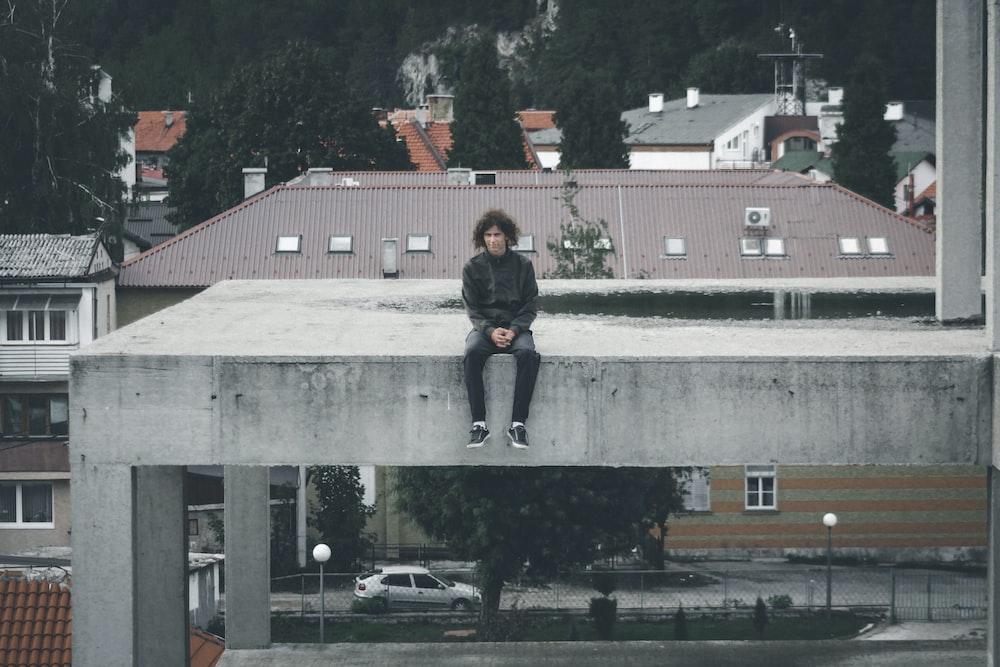 man wearing black jacket sitting on gray concrete