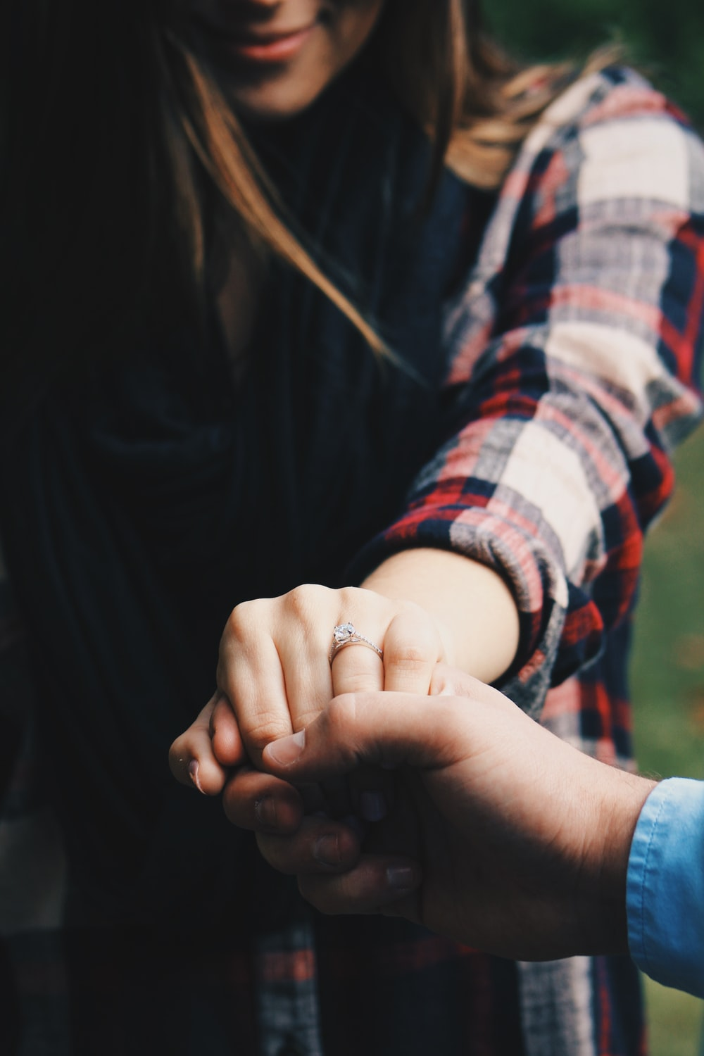 woman holding hands showing her ring