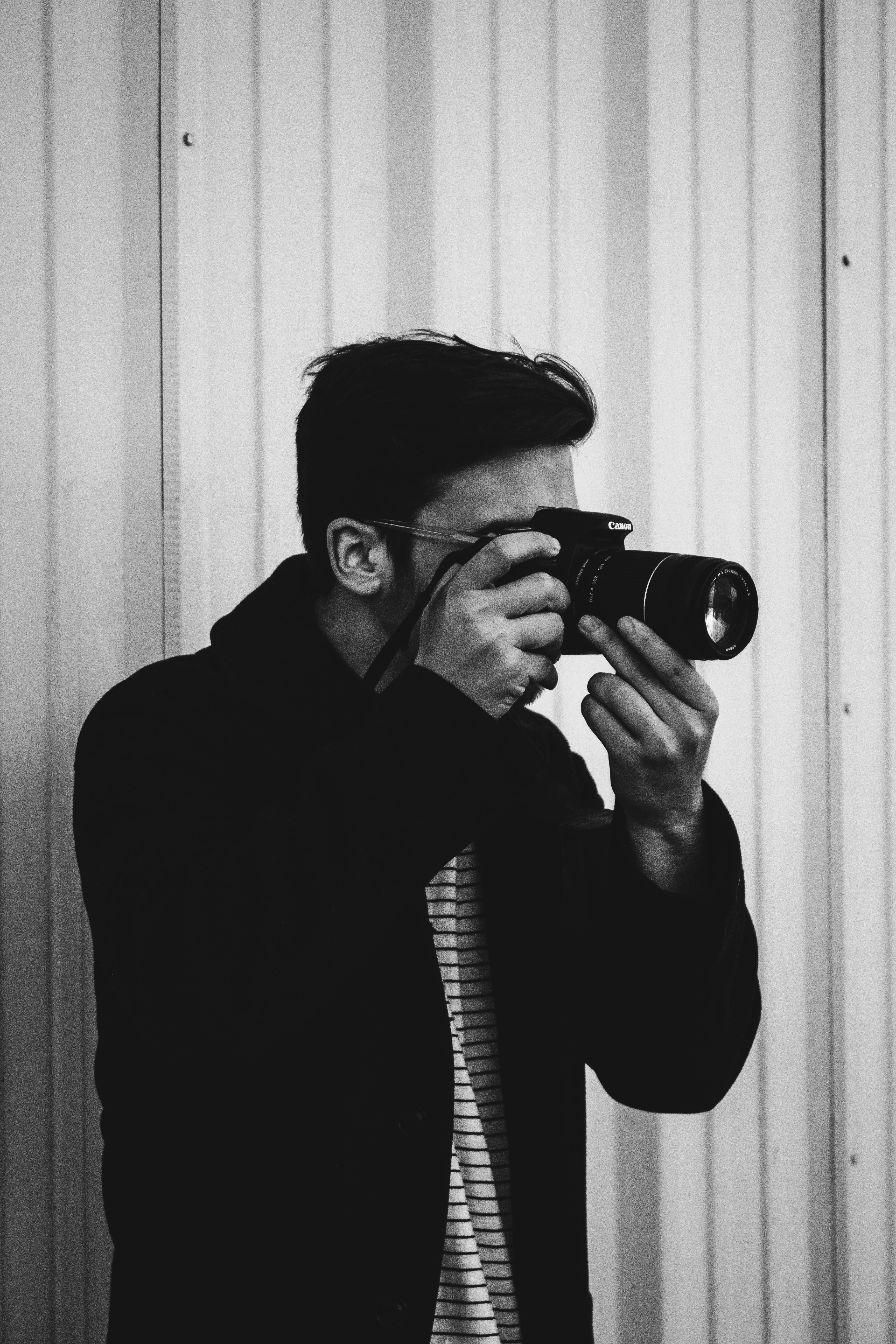 grayscale photograph of man holding DSLR camera while taking photo