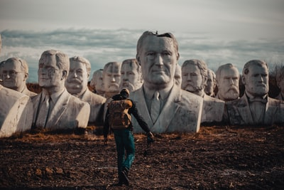 person in black hoodie walking on dirt in front of bust presidents zoom background