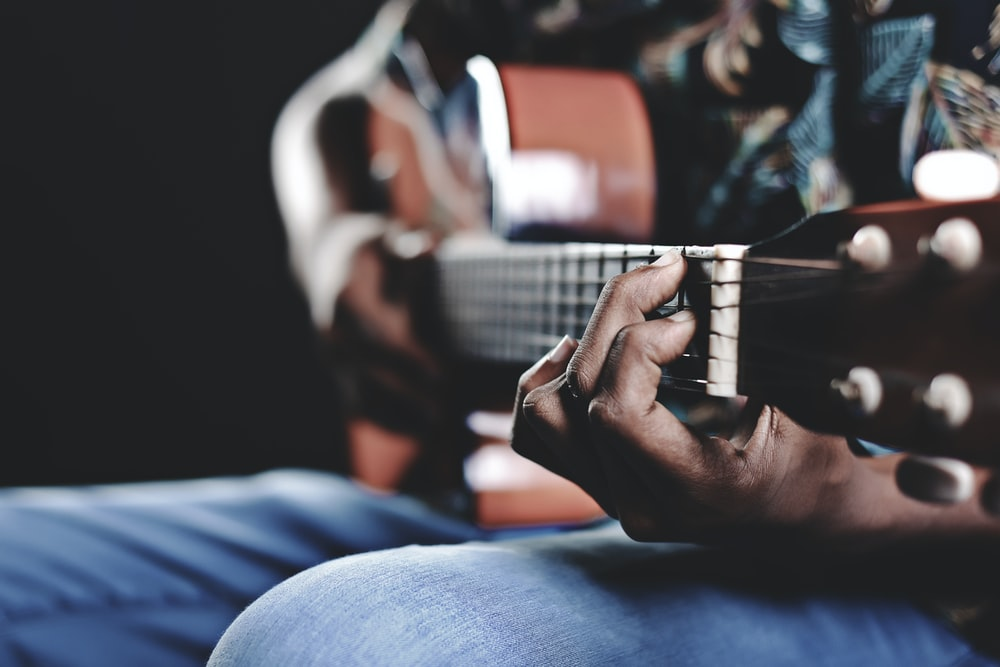 person playing a brown guitar