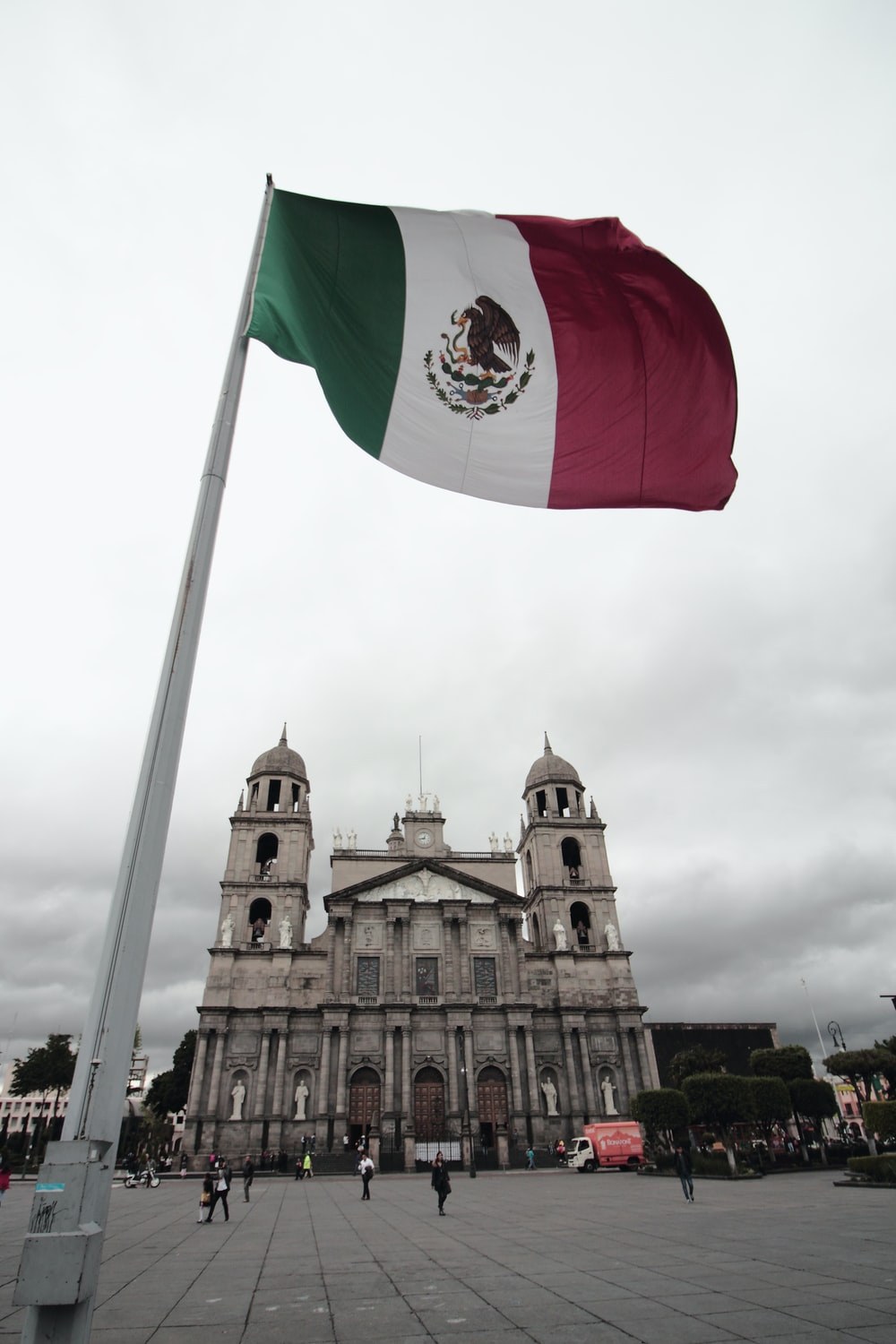 Mexico flag waving near brown concrete building at daytime