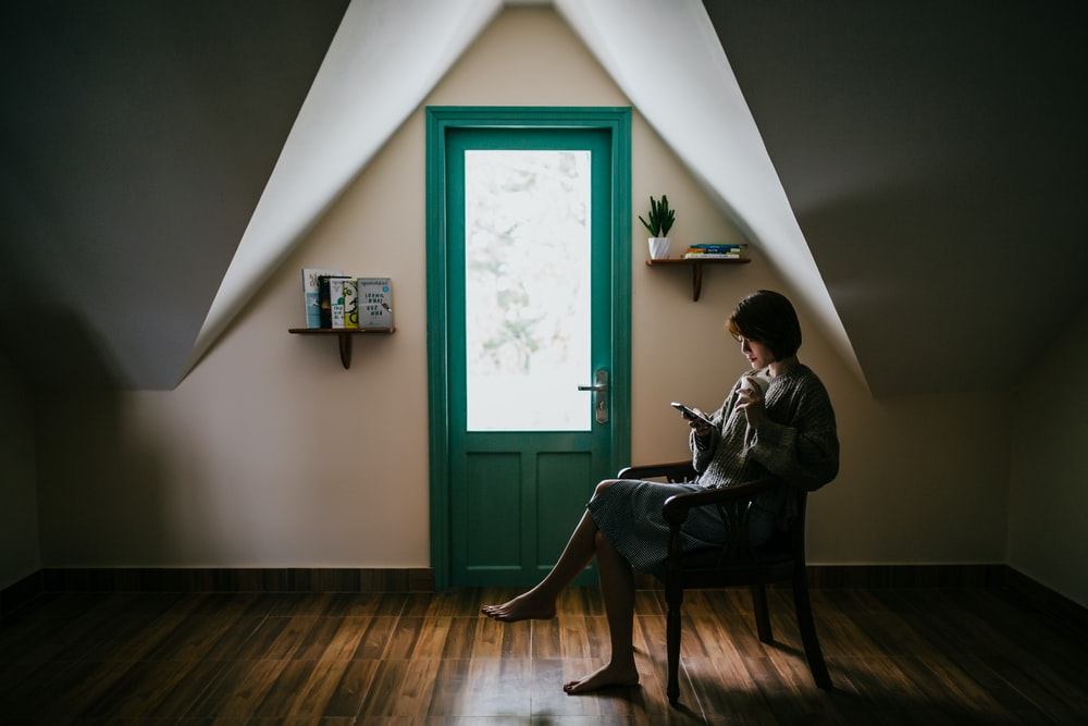 woman sitting on a chair inside white painted room