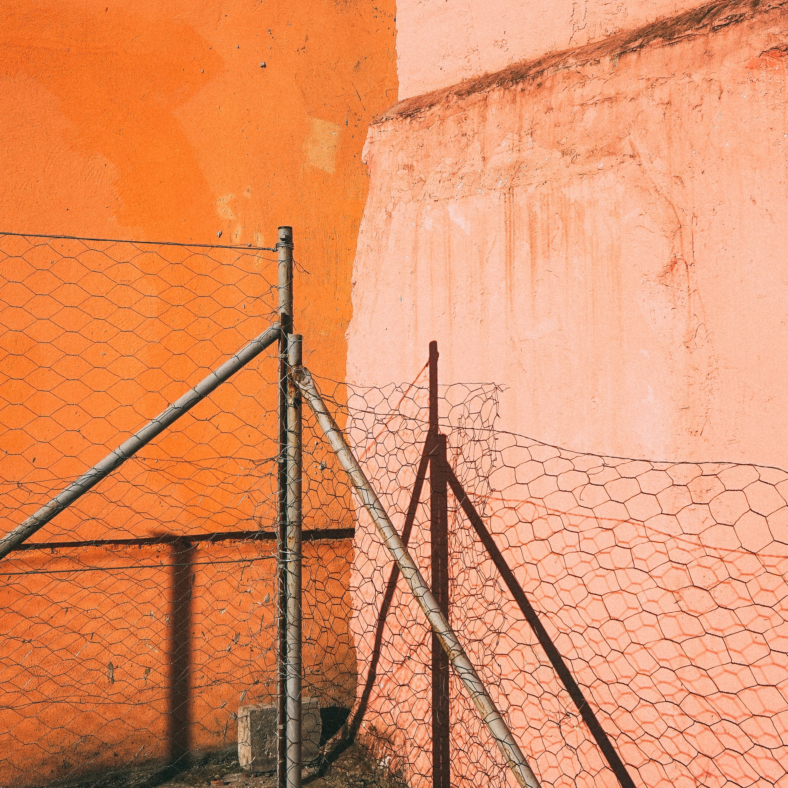 barbed wire on gray pipes near orange wall