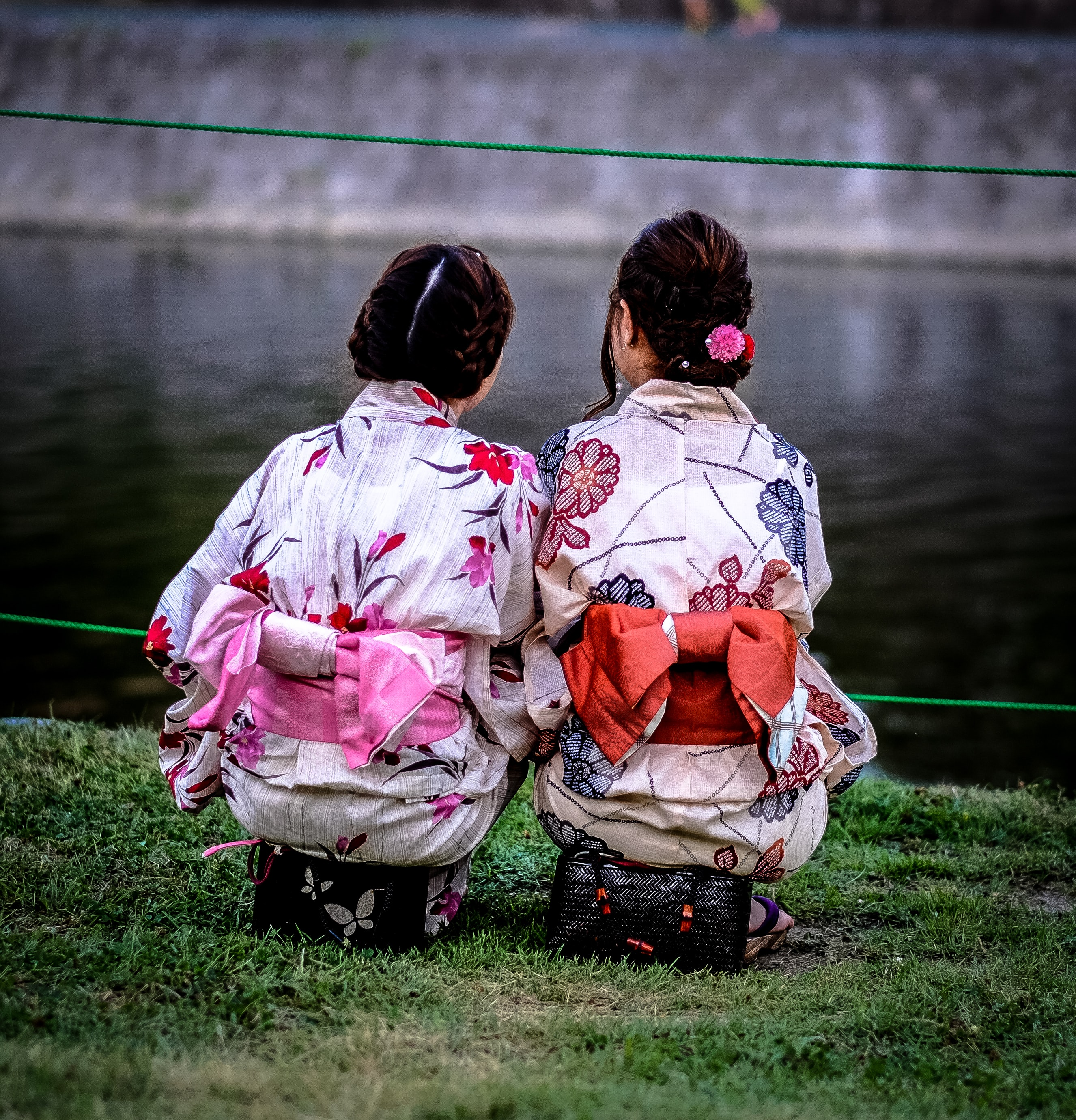 photo of two women wearing floral kimono staring at body of water