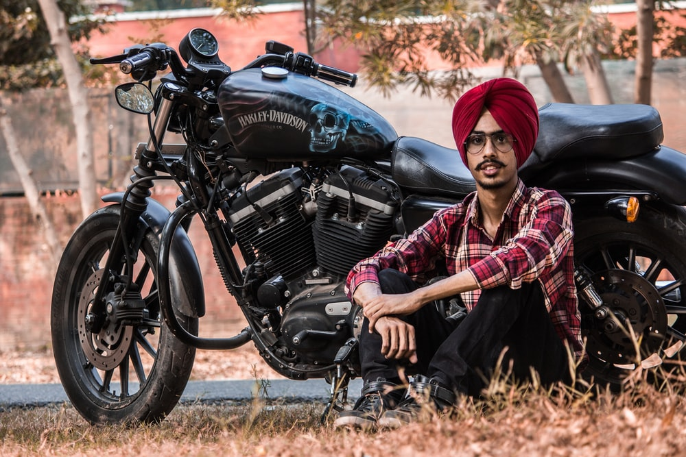 man sitting beside black standard motorcycle