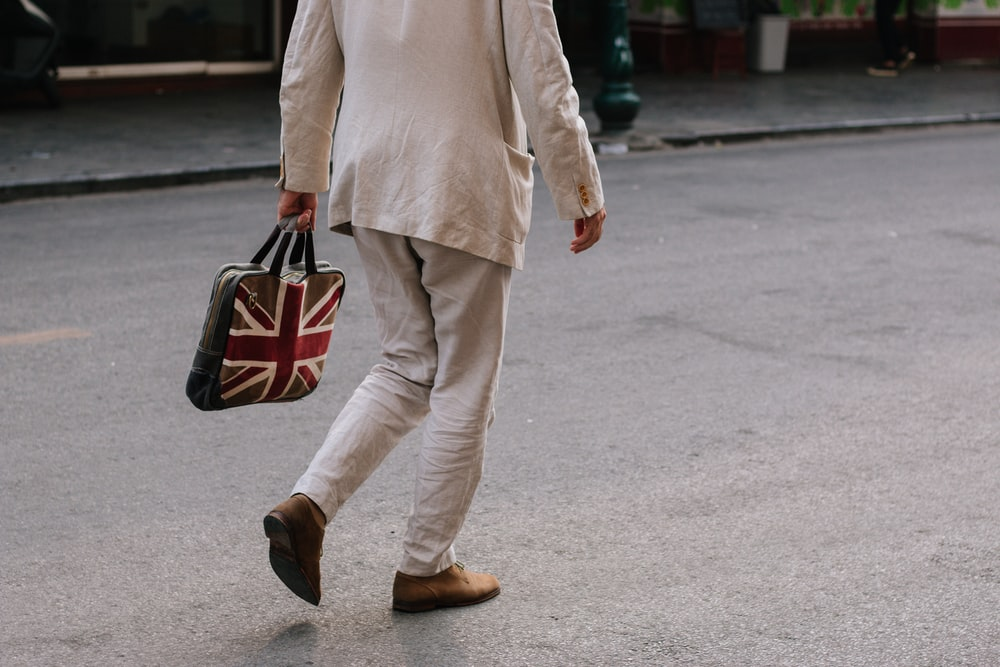 man walking while holding handbag