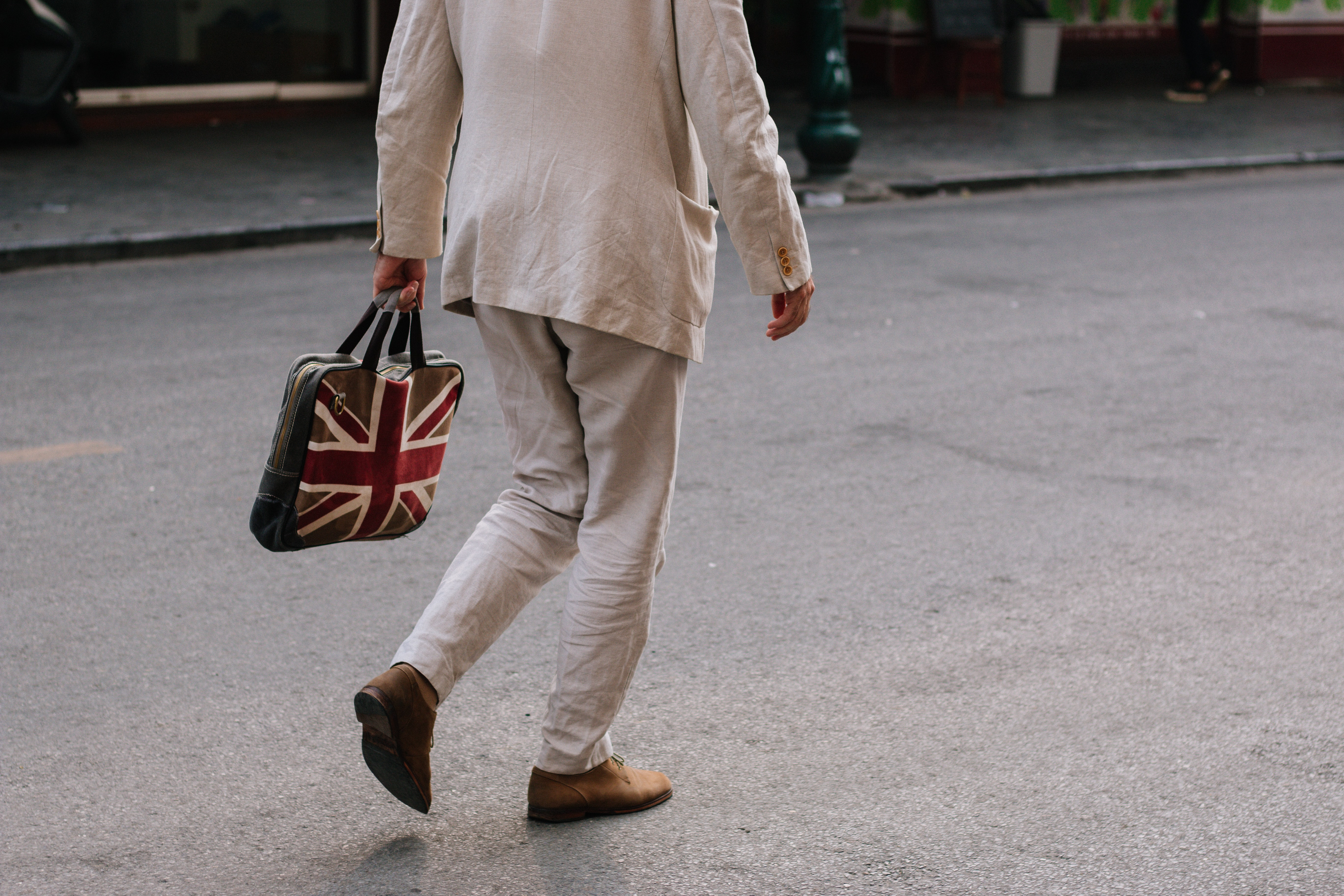 man walking while holding handbag