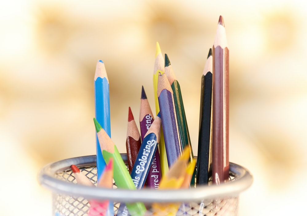 shallow focus photography of pencils on desk rack