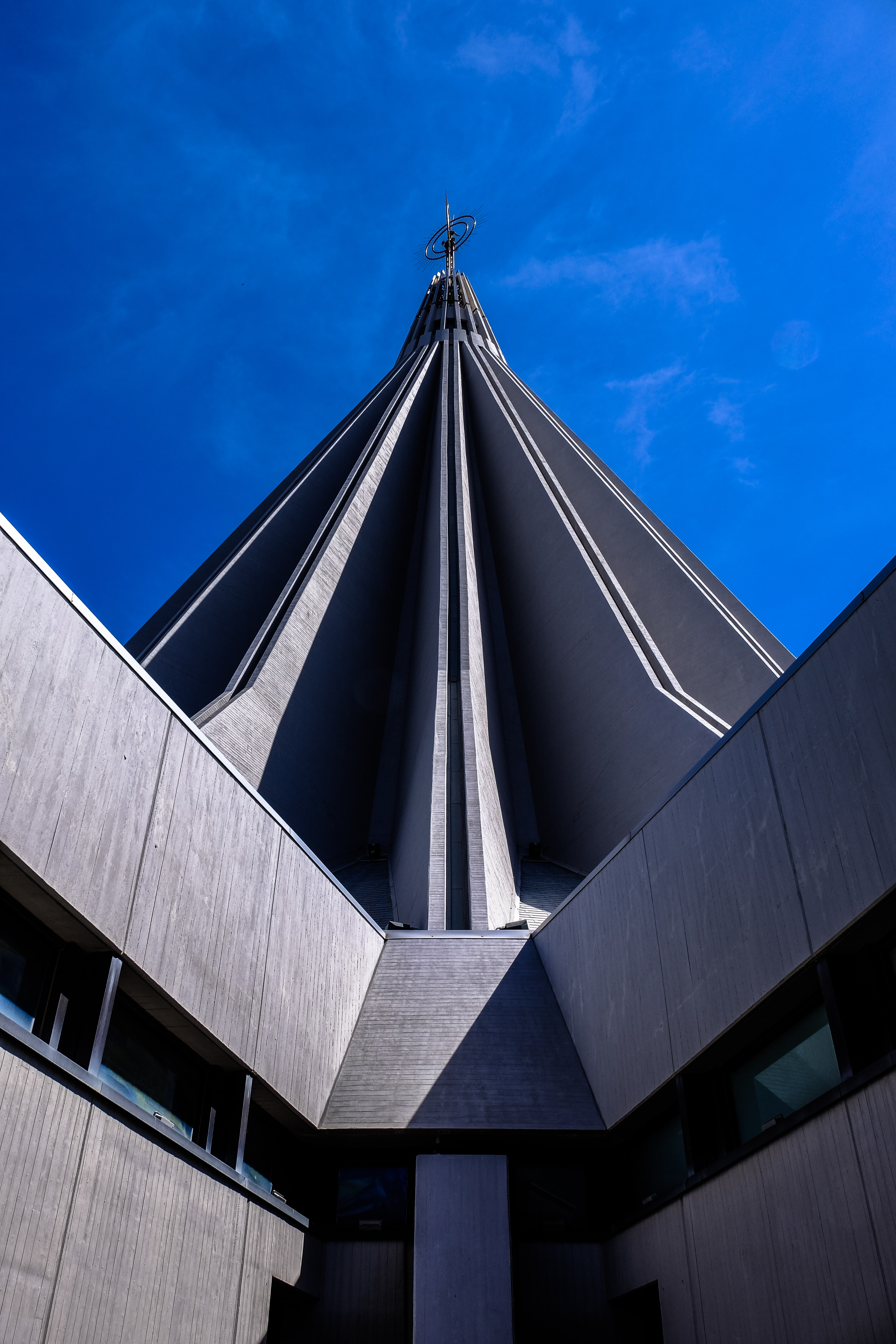 gray concrete building with circle finial under clear sky