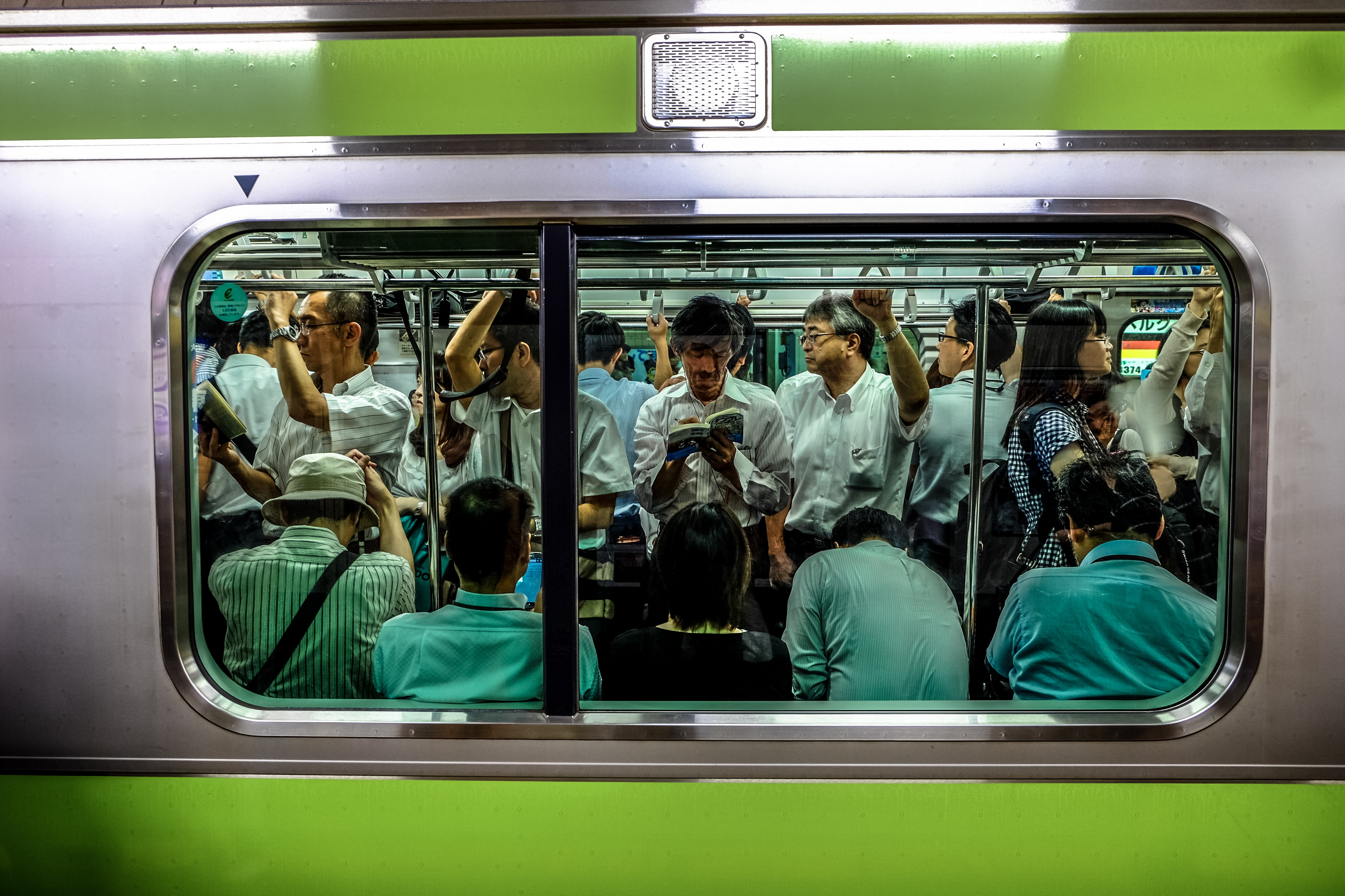 people sitting and standing inside train