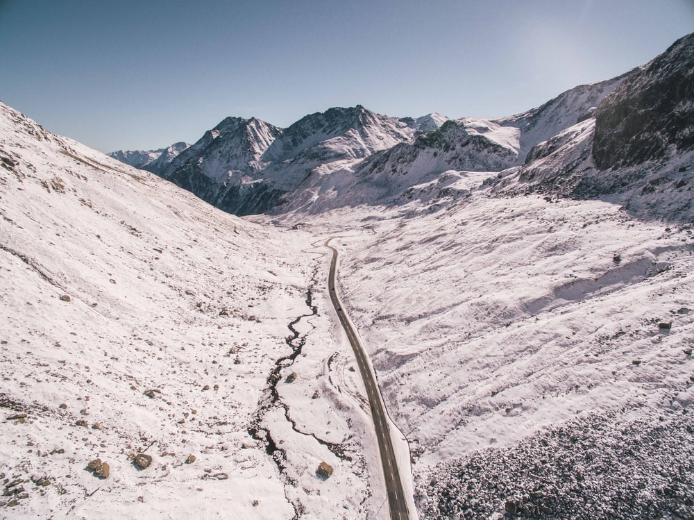 asphalt road between snow covered mountains under clear sky