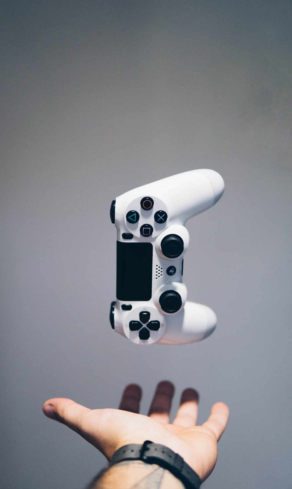 white Sony PS4 DualShock controller over person's palm