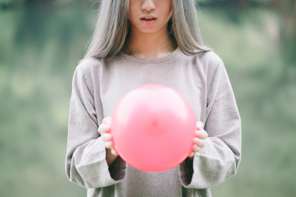 girl in grey long-sleeved shirt holding pink balloon