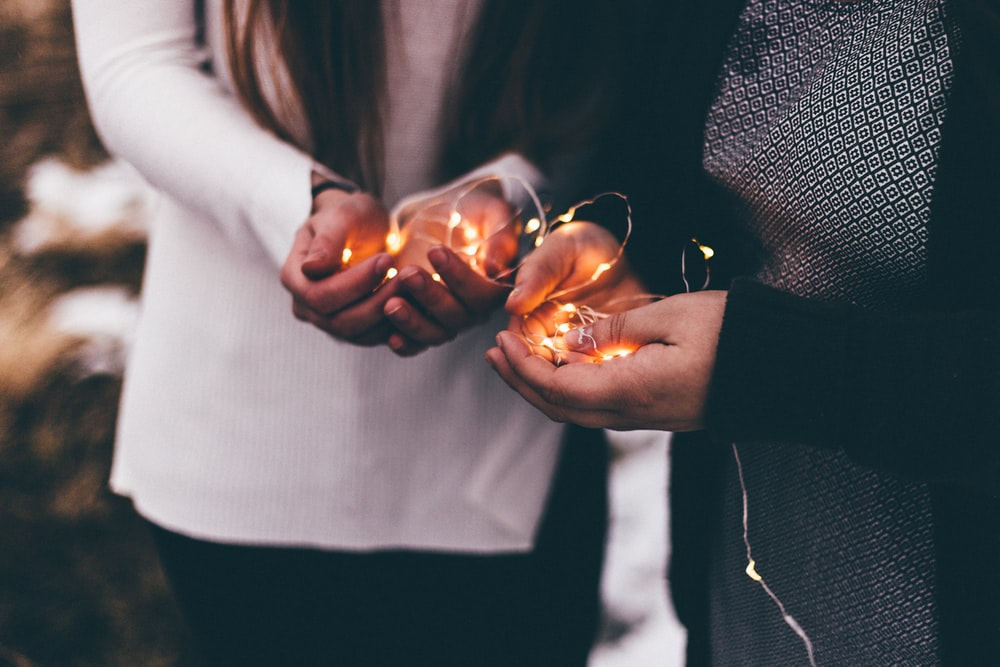 close-up photo of two person holding lighted string lights