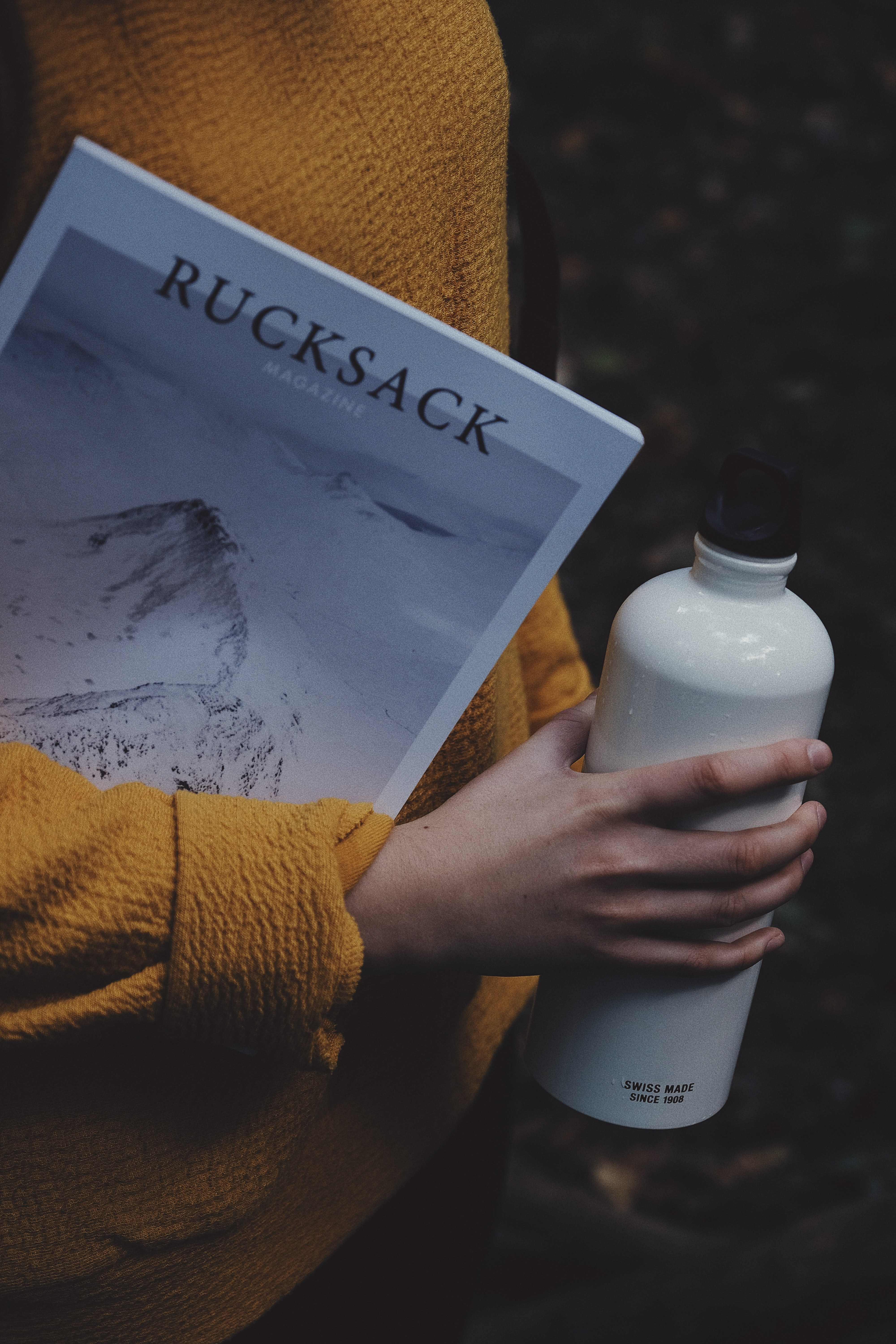 person holding white tumbler and a Rucksack magazine in between arm
