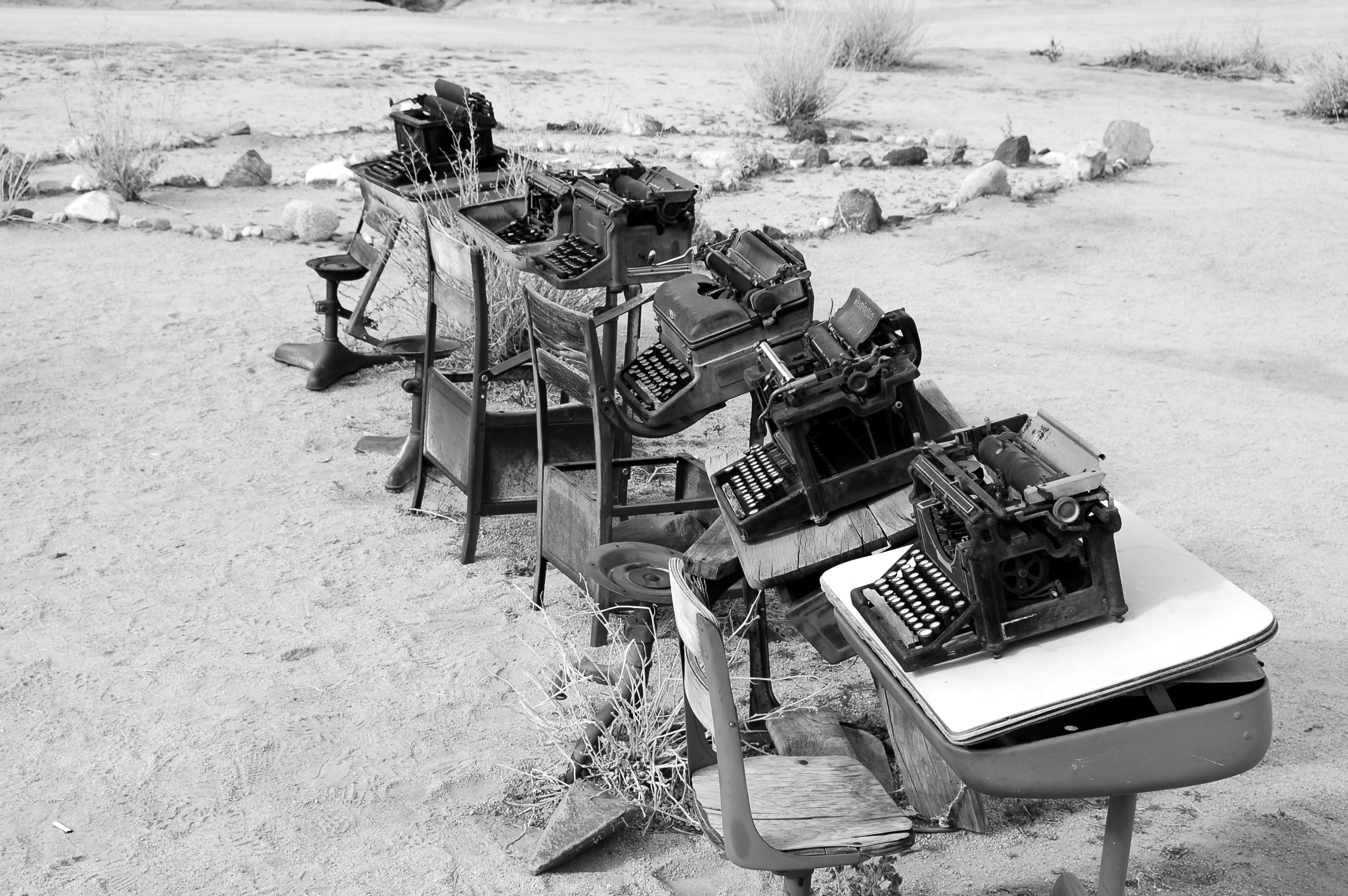 grayscale photo of typewriter on tables