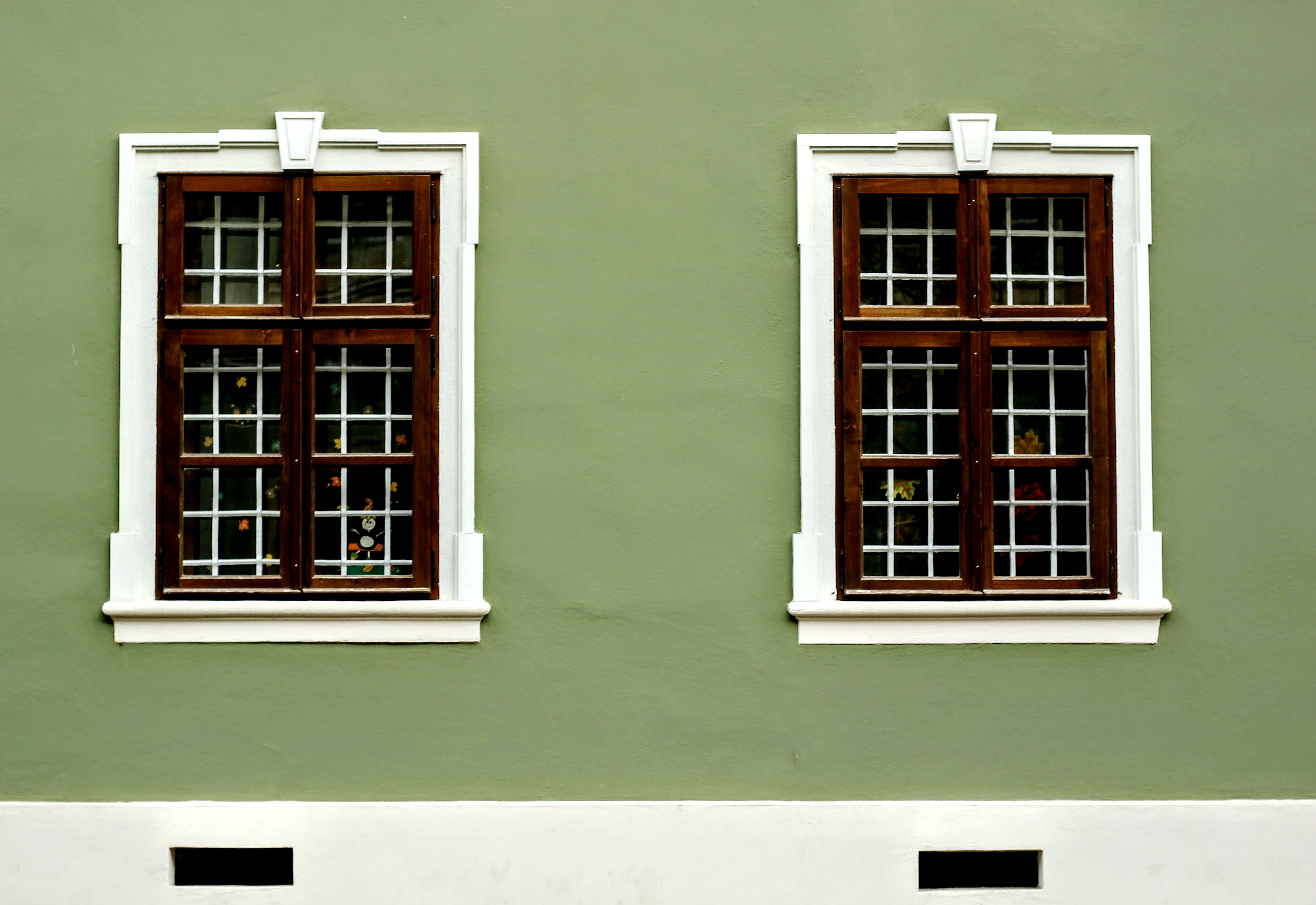 brown windows mounted in green painted wall