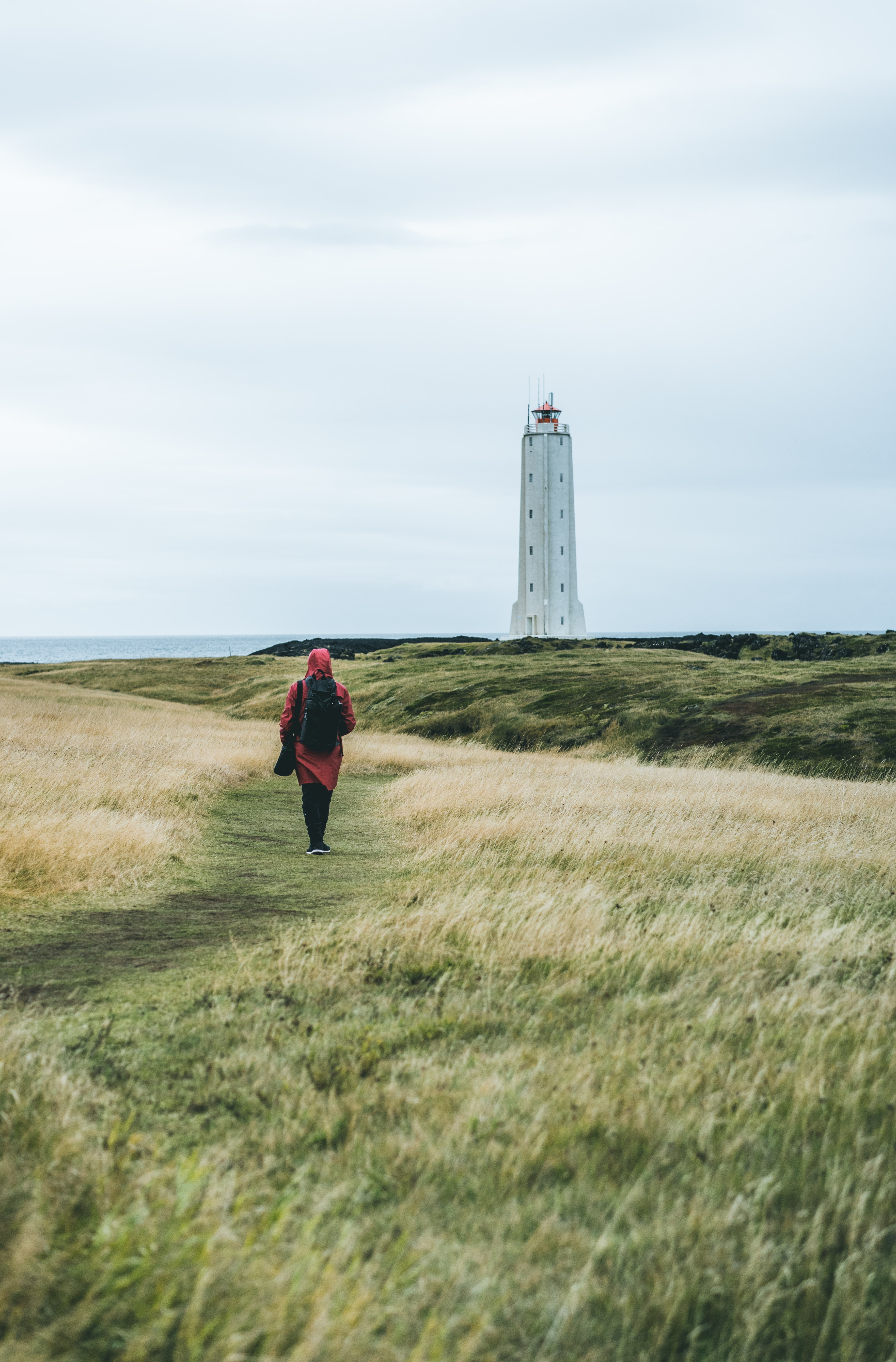 woman in red dress walks on green grass leading to white lighthouse