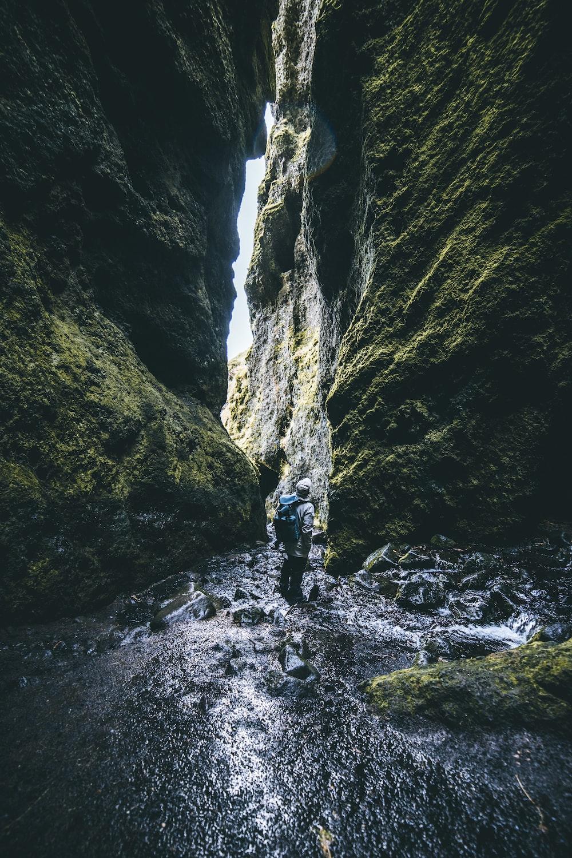 man standing in between of rock formations
