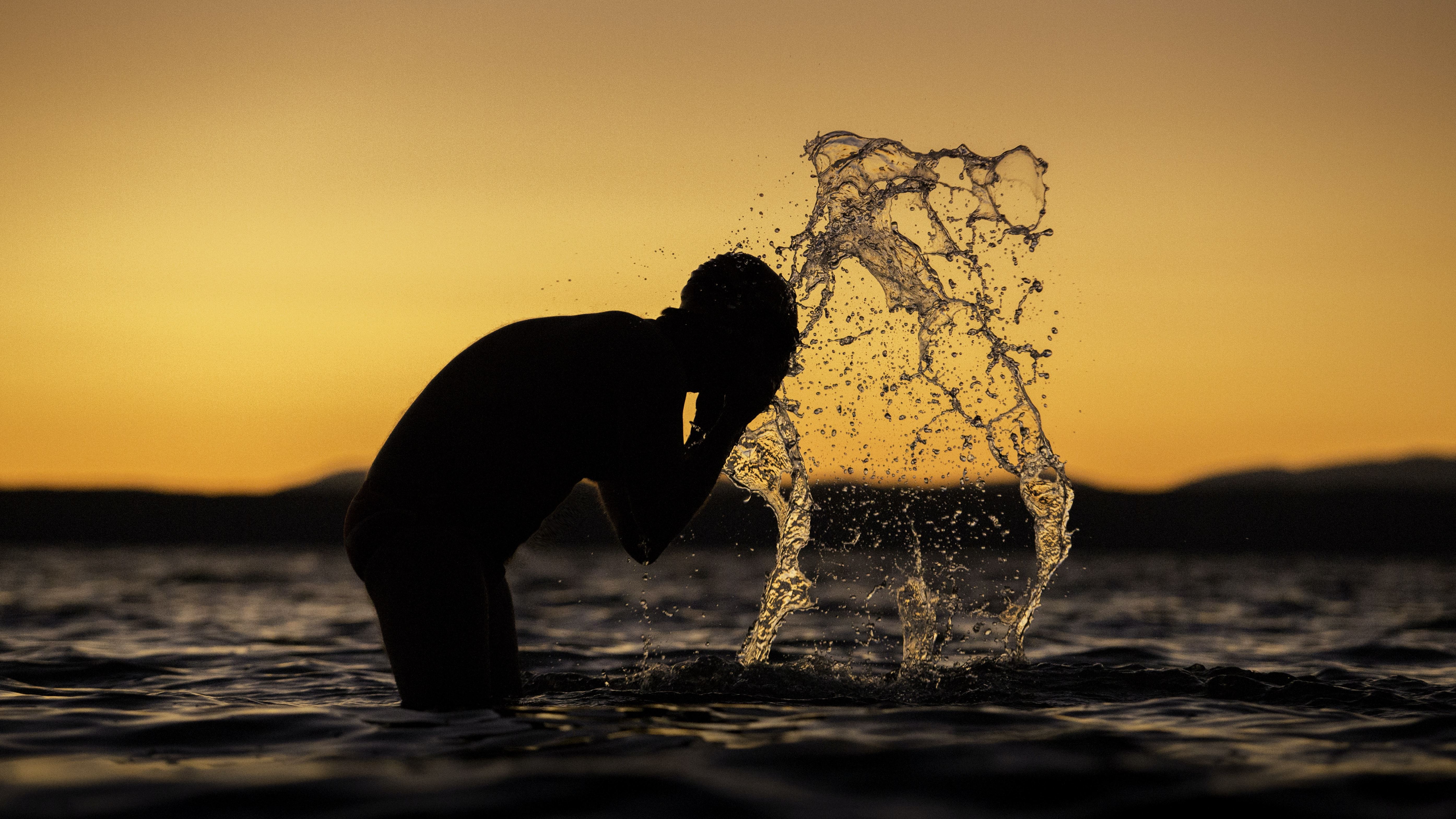 silhouette of man washing his face on body of water