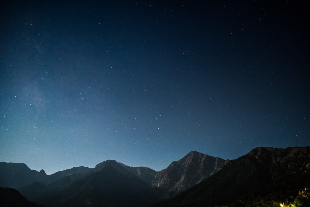 silhouette of mountains during starry night