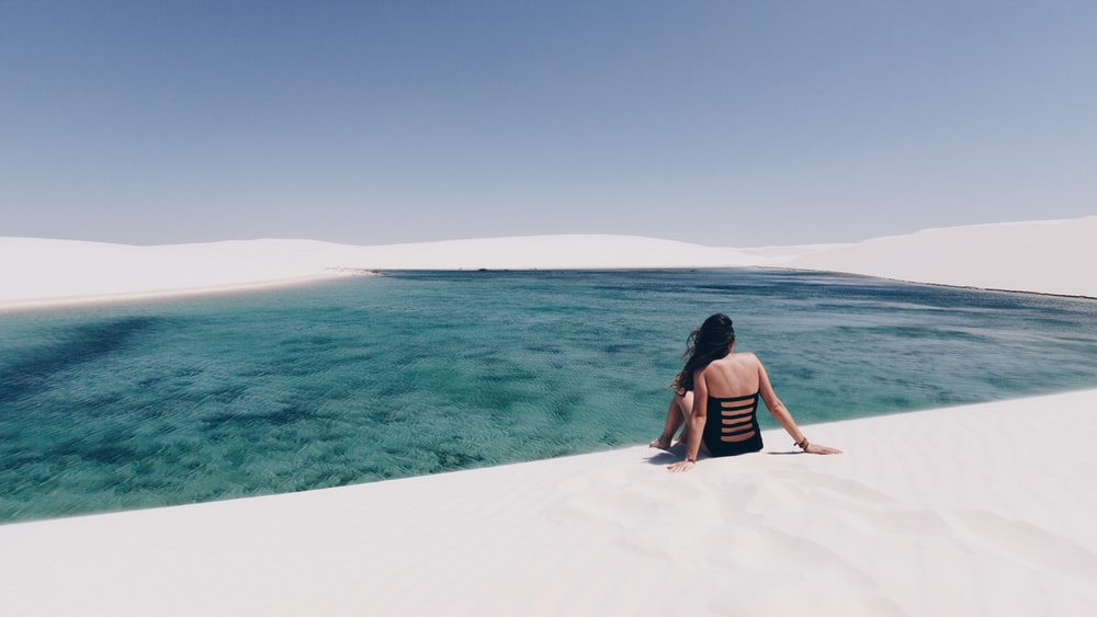 woman sitting on white sand near body of water