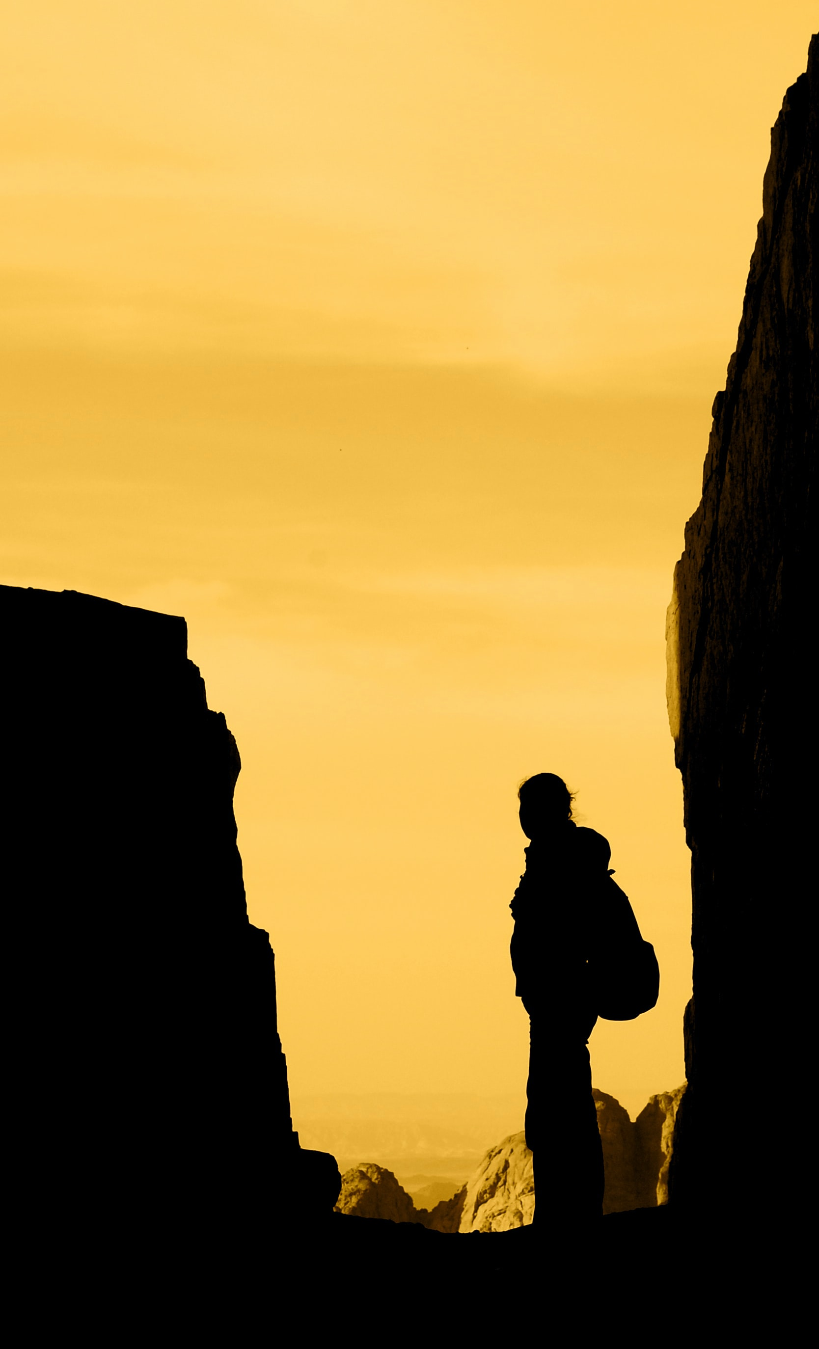 silhouette of person standing in between rocks