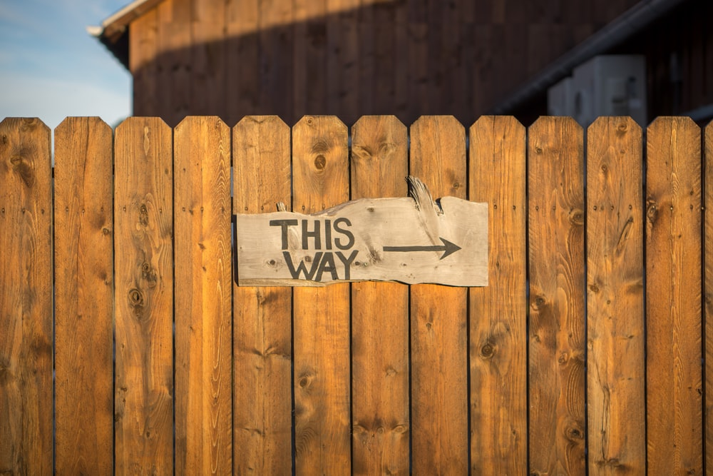 brown wooden plank fence with this way signboard