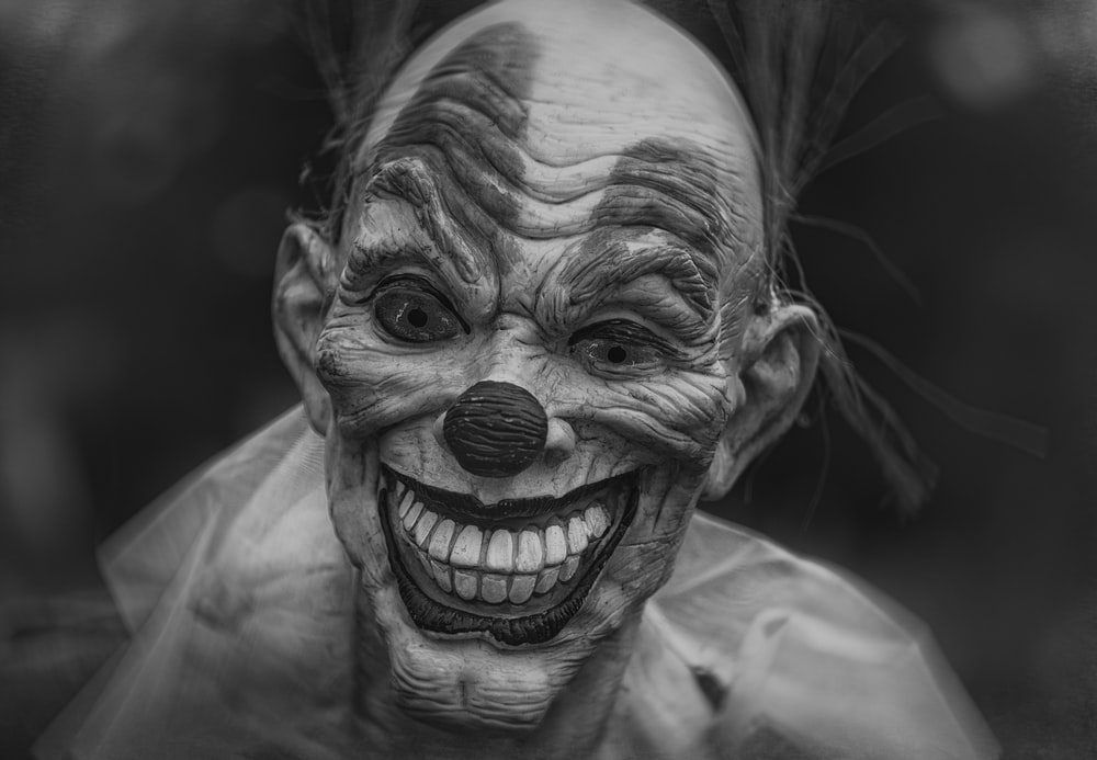 grayscale photography of person wearing clown mask