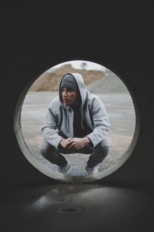 man sitting near gray tunnel during daytime