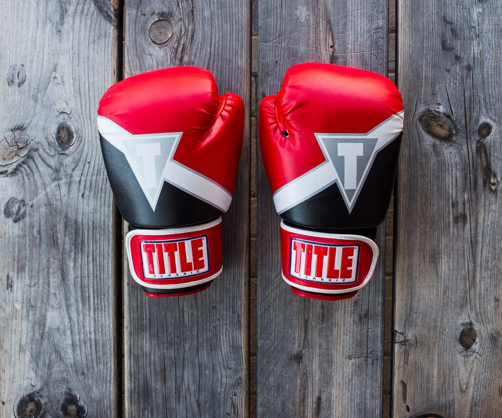 pair of red-and-black Title training gloves on grey wooden plank