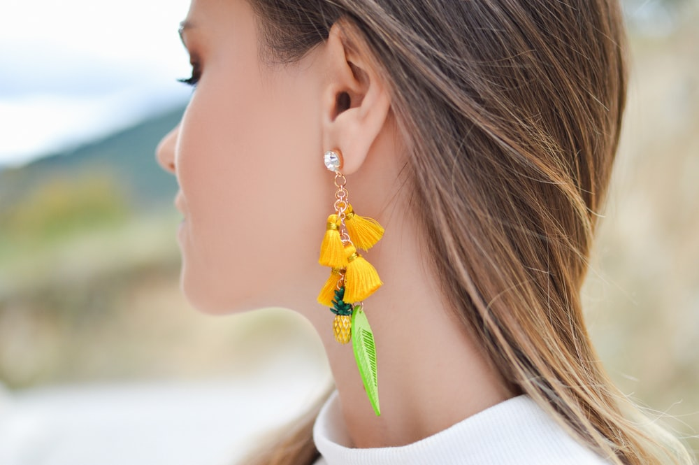 woman with yellow and green tasseled earring